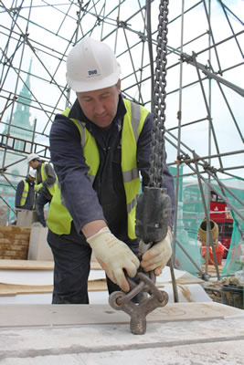 Jim attaching the hoist to the lewis pins ready to lift a stone into position